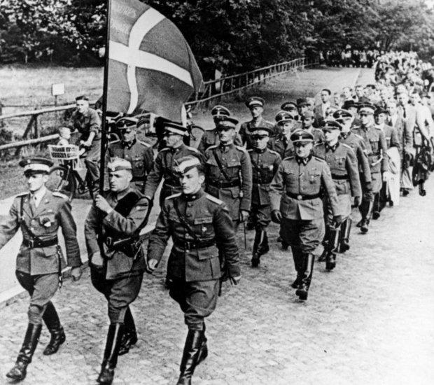 Voluntarios del Cuerpo SS Libre Danés en formación con la bandera de Dinamarca.