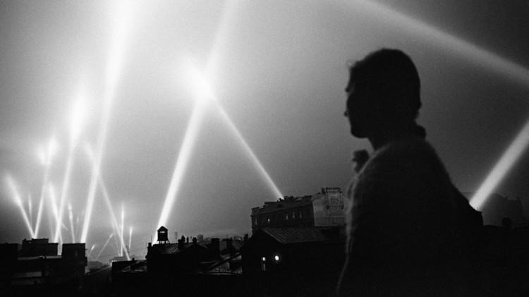 Bombardeo de Moscú por parte de la Luftwaffe. Un ciudadano ruso contempla los proyectores de luz iluminando el cielo.